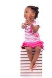 Bambina americana dell'africano nero sveglio messa in una pila di fischio Fotografia Stock