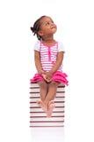 Bambina americana dell'africano nero sveglio messa in una pila di fischio Immagine Stock