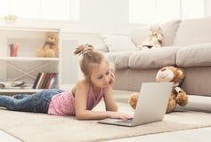 Bambina annoiata che fa compito sul computer portatile Fotografie Stock