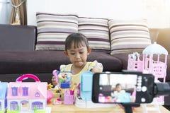 Bambina asiatica che gioca i giocattoli a casa Con la registrazione che fa video blogger immagini stock