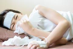 Bambina asiatica che soffia il suo naso in un tessuto con il gel freddo disposto sulla sue fronte, rinite allergica, bambino mala immagine stock
