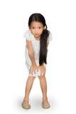 Bambina asiatica che sta con le mani sulle ginocchia fotografia stock libera da diritti