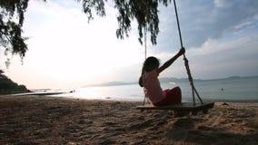 bambina asiatica del movimento lento 4K che gioca oscillazione sulla spiaggia con uguagliare luce ambientale archivi video