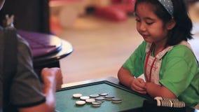 Bambina asiatica felice che gioca gioco da tavolo con l'amico, fronte di sorriso stock footage