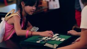 Bambina asiatica felice che gioca gioco da tavolo con l'amico, fronte di sorriso archivi video