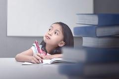 Bambina asiatica felice che pensa con il libro e la penna Immagini Stock