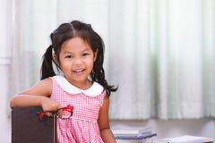 Bambina asiatica felice con il libro Immagini Stock