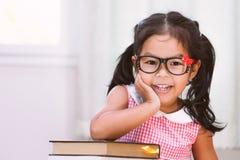 Bambina asiatica felice con il libro Fotografie Stock