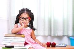 Bambina asiatica felice con il libro Immagine Stock