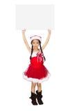 Bambina asiatica nel vestito di Natale con l'insegna in bianco immagini stock