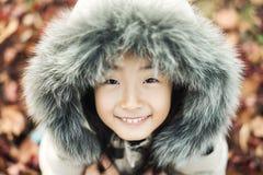 Bambina asiatica sorridente in un cappello di pelliccia di inverno Immagini Stock Libere da Diritti