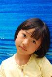 Bambina asiatica su priorità bassa blu Fotografie Stock Libere da Diritti