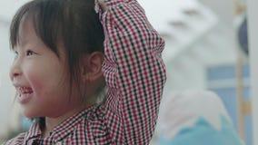 Bambina asiatica sveglia che gioca con la madre a casa La ragazza eccitata che gioca con la ripetizione dopo la bambola si divert stock footage