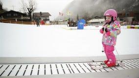 Bambina in attrezzatura di inverno che resta su Ski Conveyor Il bambino sta divertendosi lo sci di inizio Esperienza felice dello archivi video