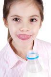 Bambina bedriegt bottiglia Di latte che Si lecca le lab stock afbeeldingen