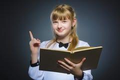 Bambina bella con il libro che ha idea isolata su fondo grigio Fotografia Stock