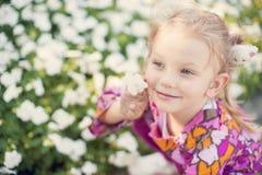 Bambina bella con un fiore Fotografia Stock