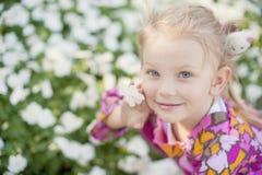 Bambina bella con un fiore Immagine Stock