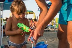 Bambina bionda caucasica che gioca sulla sabbia della spiaggia al tramonto con una pistola a acqua di plastica verde immagini stock libere da diritti