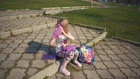 Bambina bionda che mangia il suo pranzo in parco il giorno soleggiato video d archivio