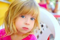 Bambina bionda che osserva gli occhi azzurri della macchina fotografica Fotografia Stock