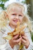 Bambina bionda che raccoglie le foglie del autmn immagini stock libere da diritti