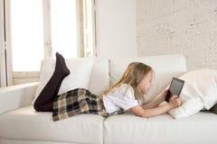 Bambina bionda che si trova sullo strato domestico del sofà facendo uso di Internet app sul cuscinetto digitale della compressa s Immagini Stock