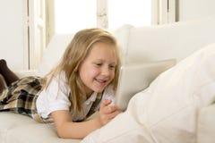 Bambina bionda che si trova sullo strato domestico del sofà facendo uso di Internet app sul cuscinetto digitale della compressa s Fotografia Stock Libera da Diritti