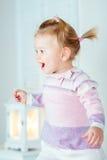Bambina bionda emozionante con la coda di cavallo che salta sul letto Fotografie Stock