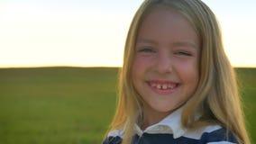 Bambina bionda felice che ride e che sorride alla macchina fotografica, giacimento di grano durante il tramonto nel fondo, allegr stock footage