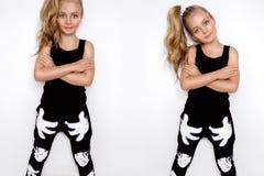 Bambina bionda sveglia in attrezzatura di sport su un fondo bianco in studio Immagini Stock