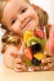 Bambina in buona salute felice con l'insalata di frutta Fotografia Stock