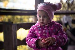 Bambina calorosamente vestita con una mela fresca rossa immagini stock libere da diritti