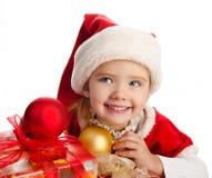 Bambina in cappello di natale con il contenitore e le palle di regalo Fotografia Stock Libera da Diritti