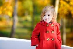 Bambina in cappotto rosso luminoso all'autunno Immagine Stock Libera da Diritti