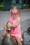 Bambina a cavalcioni su una figura dell'anatra di ferro e Fotografia Stock