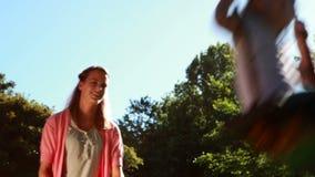 Bambina che è spinta su un'oscillazione tramite sua madre nel parco video d archivio