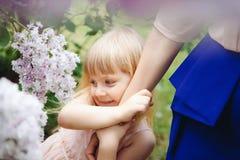 Bambina che abbraccia sua madre nel giorno di estate con i fiori intorno immagini stock libere da diritti