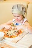 Bambina che aggiunge formaggio in pizza Immagini Stock