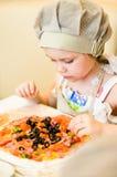 Bambina che aggiunge gli ingredienti in pizza Immagini Stock