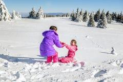 Bambina che aiuta il suo amico a alzarsi sulla neve Immagine Stock