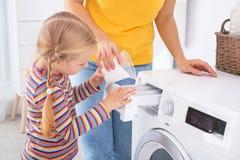 Bambina che aiuta sua madre a fare lavanderia immagini stock libere da diritti