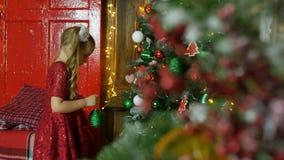Bambina che appende sui giocattoli dell'albero di Natale stock footage