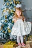 Bambina che apre un regalo a casa nel salone Immagine Stock