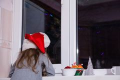 Bambina che aspetta racconto scuro del mandarino di Natale di Santa Claus di inverno magico della finestra fotografie stock
