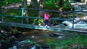 Bambina che attraversa il ponte pericoloso sopra un fiume della montagna - scorra attraversando la foresta verde spessa, Bistrisk stock footage