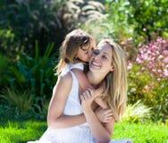 Bambina che bacia la sua madre Fotografia Stock