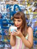 Bambina che beve il tè contro la parete di graffity Immagine Stock