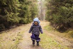 Bambina che cammina attraverso il legno Immagine Stock Libera da Diritti