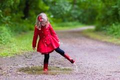 Bambina che cammina nella pioggia Immagine Stock